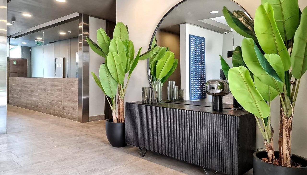 mesón con espejo y plantas del hall edificio Las Dalias