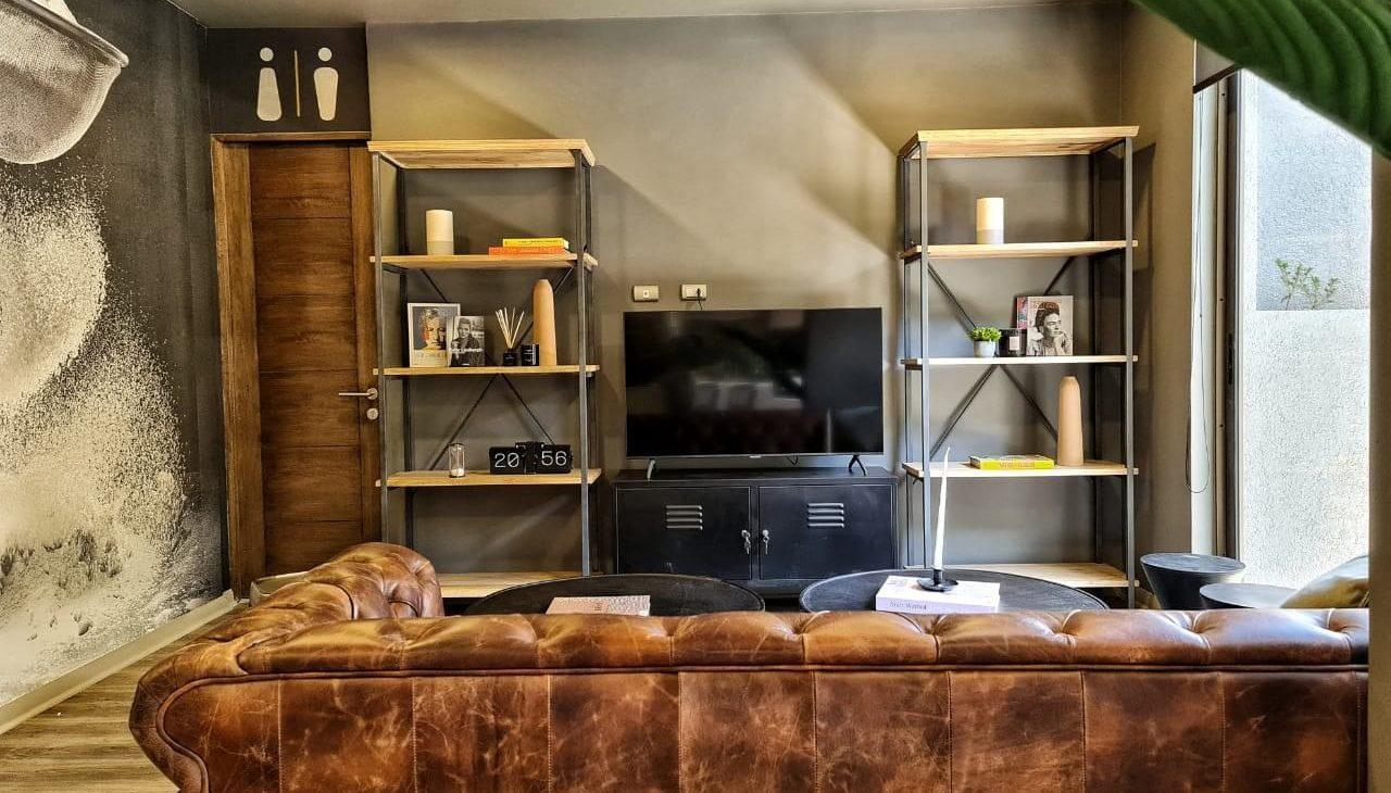 sillón con televisor y repisas social room del edificio
