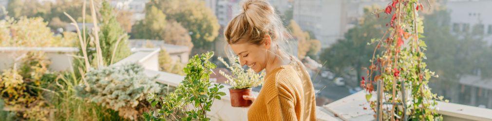 mujer cuidando sus plantas en la terraza