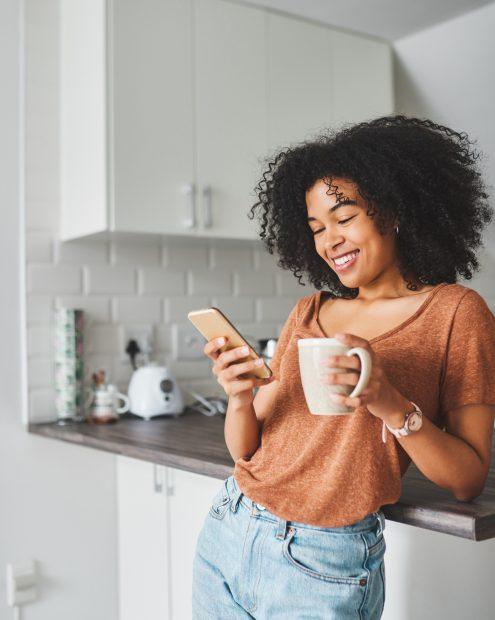 mujer tomando café y viendo su teléfono