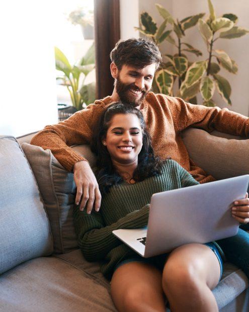 pareja sentada en un sillón viendo un notebook